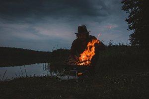 Man making fire at a lake