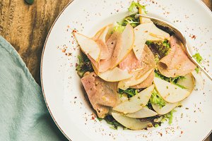 Fresh salad with smoked turkey ham and pear, wooden background