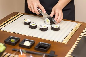 Woman chef cutting sushi rolls