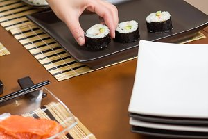 Woman chef placing sushi rolls