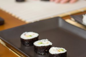 Japanese sushi rolls on a black tray