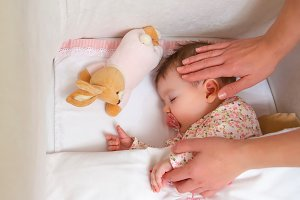 Hands of mother caressing baby