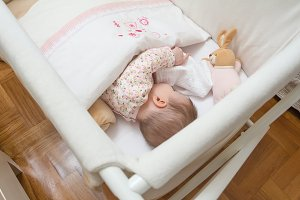 Baby girl sleep in cot with pacifier