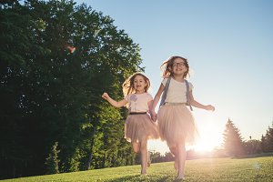 Two joyful girls running against the