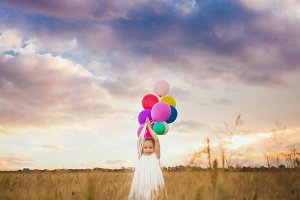 girl holds balloons
