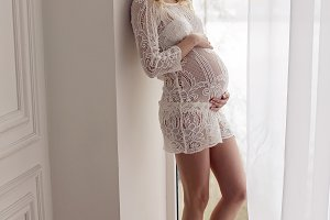 pregnant blonde girl in white lace dress standing at home