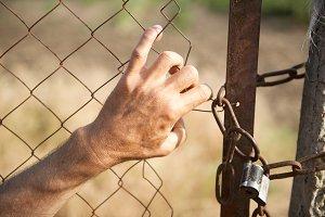 A man's hand breaks metal grid