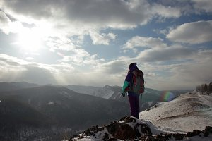 A lonely young woman tourist stands on the edge of a cliff and enjoys the scenery of the mountains.