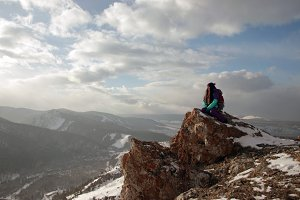 A lonely young woman sits on the edge of a cliff and enjoys the scenery of the mountains.