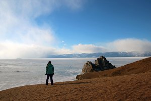 A young woman stands on the shore of the frozen lake Baikal and enjoys the scenery.
