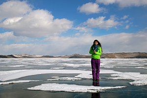A young beautiful woman stands on the ice of lake Baikal and smiles.