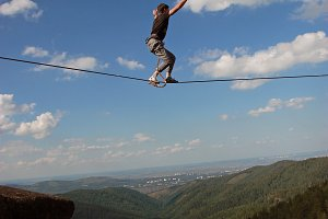 A young man ropewalker balancing over the abyss.