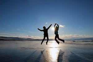 Silhouettes of happy young people jumping over the ice of lake Baikal at sunset.
