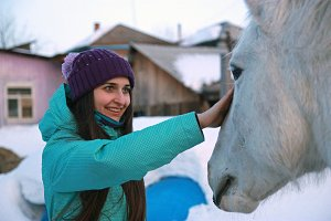 A young beautiful woman strokes a horse and smiles.