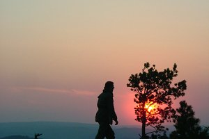 Silhouette of a man on mountain top at sunset background.