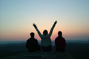 Three friends sit on top of the mountain and enjoy the sunset.