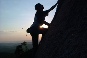 Silhouette of a young male climber climbing to the top of the cliff at sunset without insurance.