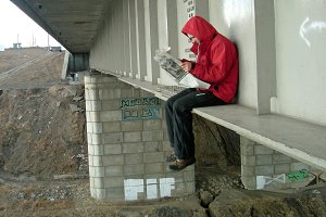Crazy man sits on the edge of the bridge and reads the newspaper.
