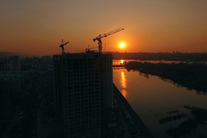 Aerial shot of silhouettes of construction cranes at sunset on the river Bank.
