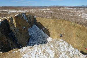 Aerial shot of the brave man jumps from the top of the cliff into the abyss.
