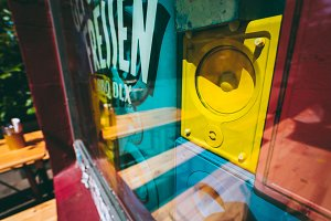 Close up of old retro multi colored sound speakers boxes behind the shop window vitrine on the city street