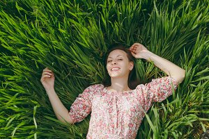 Young smiling tender beautiful woman in light patterned dress lying on grass looking up resting in sunny weather in field on bright green background. Spring nature. Lifestyle, leisure concept.