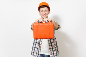Young smiling handsome man in protective orange hardhat holding case with instruments or toolbox isolated on white background. Instruments, tools for renovation apartment room. Repair home concept.