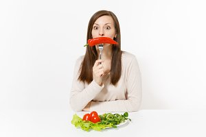 Fun woman at table with leaves salad lettuce, tomatos on plate, pepper on fork isolated on white background. Proper nutrition, vegetarian food, healthy lifestyle dieting concept. Area to copy space.
