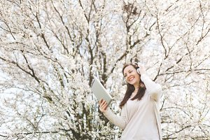 Young smiling beautiful woman in light casual clothes with headphones listening music holding tablet pc computer in city garden or park on blooming tree background. Spring flowers. Lifestyle concept.