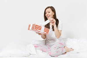 Young brunette woman sitting in bed with red striped gift box, white sheet, pillow, wrapping in blanket isolated on white background. Happy female spending time in room. Rest relax good mood concept.
