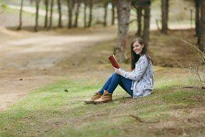 Young smiling beautiful woman in casual clothes sitting on ground studying reading book in big city park or forest on green blurred background. Student learning, education. Lifestyle, leisure concept.