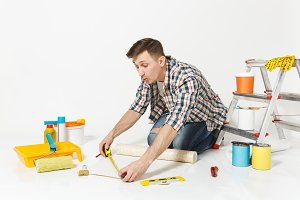 Young man sitting on floor with roll of wallpaper, measure tape, pencil, instruments for renovation apartment room isolated on white background. Gluing accessories, painting tools. Repair home concept