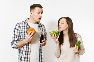 Couple man and woman standing with green detox smoothies, salad in glass bowl, burger, cola in glass bottle isolated on white background. Proper nutrition, healthy lifestyle, fast food, choice concept