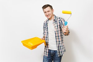 Young smiling handsome man in casual clothes holding paint tray and paint roller for wall painting isolated on white background. Instruments, tools for renovation apartment room. Repair home concept.