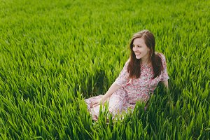 Young brunette smiling attractive woman in light patterned dress sitting on grass looking aside resting in sunny weather in field on bright green background. Spring nature. Lifestyle, leisure concept.