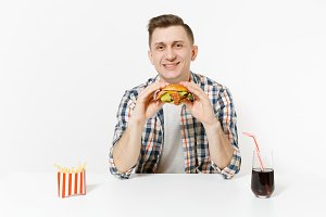 Handsome smiling young man sitting at table with burger, french fries, cola in glass isolated on white background. Proper nutrition or American classic fast food. Advertising area with copy space.