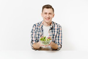 Man sits at table with green detox smoothies, salad in glass bowl, cucumber, burger, fries, cola in glass isolated on white background. Proper nutrition, healthy lifestyle, fast food, choice concept.