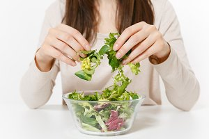 Close up cropped woman with green leaves salad in glass bowl, in hands isolated on white background. Proper nutrition, vegetarian food, healthy lifestyle, dieting concept. Advertising area, copy space