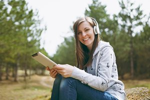 Young smiling beautiful woman in casual clothes with headphones sitting on stone using tablet pc computer in city park or forest on green blurred background. Student lifestyle, leisure concept.