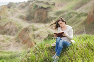 Young brunette calm woman in light casual clothes sitting on grass studying reading book on green field background. Student learning, education. Beautiful landscape. Lifestyle, leisure concept.
