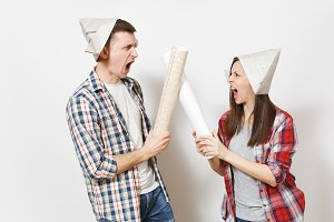 Young irritated woman, man in casual clothes holding wallpaper rolls and quarrelling. Couple isolated on white background. Instruments, accessories for renovation apartment room. Repair home concept.