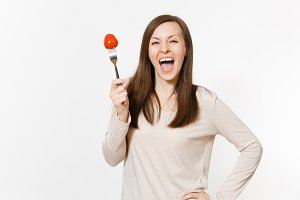 Smiling fun vegan woman holds in hand red fresh tomato on fork isolated on white background. Proper nutrition, vegetarian food, healthy lifestyle, vegetable concept. Advertising area with copy space.