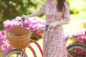 Portrait of smiling young woman in long pink floral dress stop to riding on vintage bike with basket for purchases on flowers background outdoors. Pretty female recreation time in spring, summer park