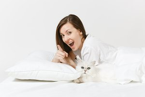 Calm young woman lying in bed with white cute Persian silver chinchilla cat, sheet, pillow, blanket on white background. Beauty female spending time in room. Rest, relax, good mood concept. Copy space