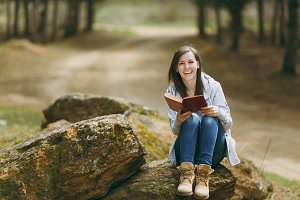 Young laughing beautiful woman in casual clothes sitting on stone studying reading book in city park or forest on green blurred background. Student learning, education. Lifestyle, leisure concept.