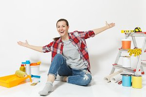 Woman in casual clothes spreading hands, sit on floor with instruments for renovation apartment room isolated on white background. Wallpaper, accessories for gluing, painting tools. Concept of repair.