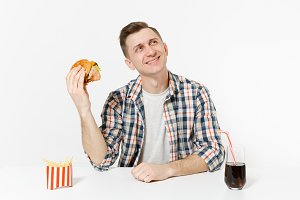 Smiling young man in shirt sitting at table with burger, french fries, cola in glass isolated on white background. Proper nutrition or American classic fast food. Advertising area with copy space.