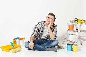 Man in casual clothes dreamily looks up, sitting on floor with instruments for renovation apartment isolated on white background. Wallpaper, gluing accessories, painting tools. Repair home concept.