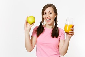 Beautiful fun happy woman holding in hands green apple and orange fresh juice in glass isolated on white background. Proper nutrition, dieting concept. Copy space for advertisement. Advertising area.