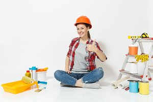 Woman in orange protective helmet sitting on floor with instruments for renovation apartment room isolated on white background. Wallpaper, accessories for gluing, painting tools. Repair home concept.
